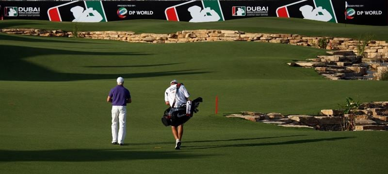 DUBAI, UNITED ARAB EMIRATES - NOVEMBER 19:  Simon Dyson of England walks with his caddie on the 18th hole during the first round of the Dubai World Championship on the Earth Course, Jumeirah Golf Estates on November 19, 2009 in Dubai, United Arab Emirates.  (Photo by Andrew Redington/Getty Images)