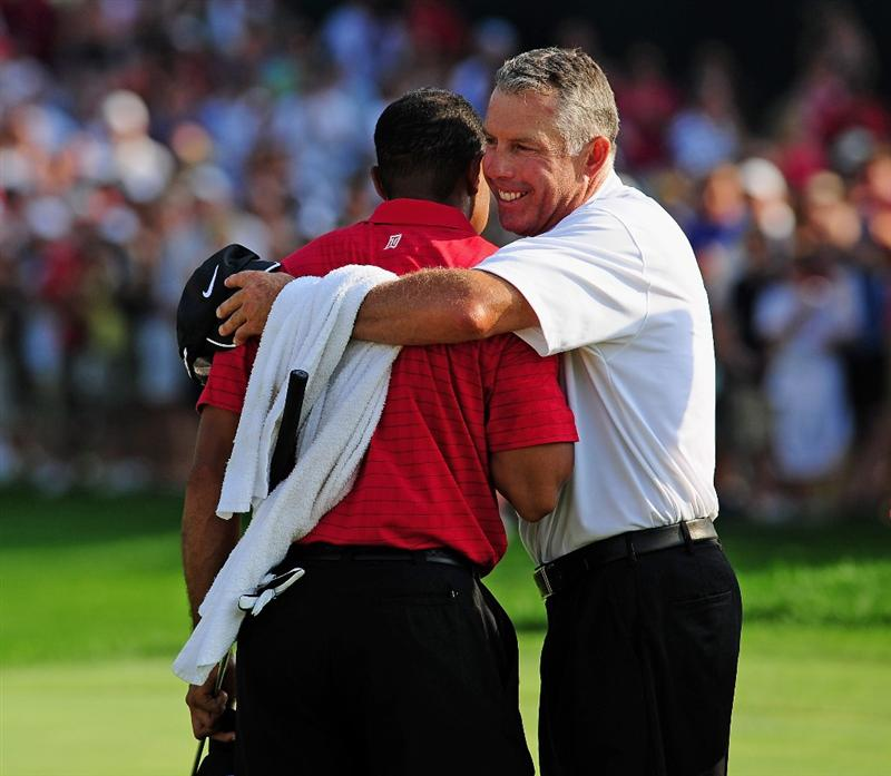 AKRON, OH - AUGUST 09:  Tiger Woods of USA is congratulated by chis caddy Steve Williams on the 18th hole during the final round of the World Golf Championship Bridgestone Invitational on August 9, 2009 at Firestone Country Club in Akron, Ohio.  (Photo by Stuart Franklin/Getty Images)