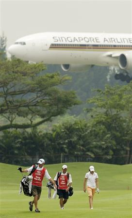 SINGAPORE - MARCH 07:  Juli Inkster of the USA walks with her caddie on the par five 15th hole as a plane flys overhead during the third round of HSBC Women's Champions at the Tanah Merah Country Club on March 7, 2009 in Singapore.  (Photo by Victor Fraile/Getty Images)