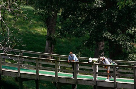 SILVIS, IL - JULY 10:  Tim Petrovic, Jerry Kelly and Petrovic's caddie look over the side of a bridge as they cross over to the fifth tee during the first round of the 2008 John Deere Classic at TPC at Deere Run on Thursday, July 10, 2008 in Silvis, Illinois.  (Photo by Kevin C. Cox/Getty Images)