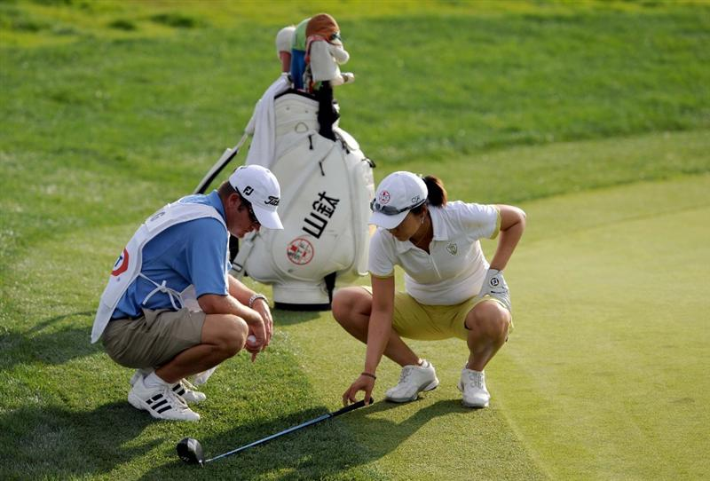 NORTH PLAINS, OR - AUGUST 28: Candie Kung of Taiwan and her caddy Jeff King measure for relief under a special rule for the step cut rough on the 18th hole during the first during the first round of the Safeway Classic on August 28, 2009 at Pumpkin Ridge Golf Club in North Plains, Oregon. Kang finished the day tied for 4th with a 6 under par 66. (Photo by Steve Dykes/Getty Images)