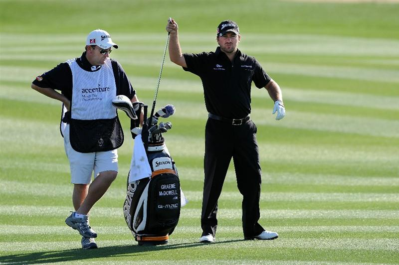 MARANA, AZ - FEBRUARY 24:  Graeme McDowell of Northern Ireland pulls a club on the fairway of the second hole as caddie Ken Comboy looks on during the second round of the Accenture Match Play Championship at the Ritz-Carlton Golf Club on February 24, 2011 in Marana, Arizona.  (Photo by Stuart Franklin/Getty Images)