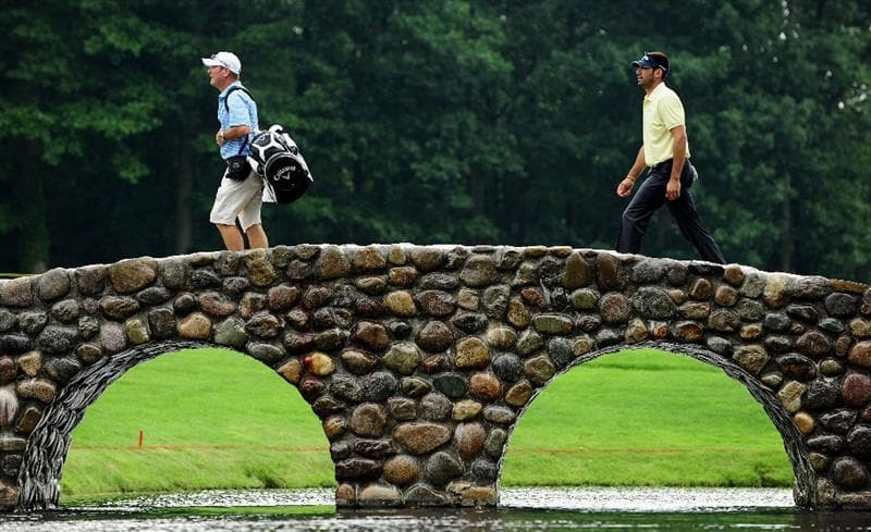 AKRON, OH - AUGUST 04:  Alvaro Quiros of Spain and caddie Alastair Mclean walk over a bridge during a practice round of the World Golf Championship Bridgestone Invitational on August 4, 2009 at Firestone Country Club in Akron, Ohio.  (Photo by Stuart Franklin/Getty Images)