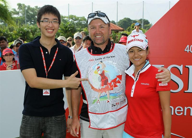SINGAPORE - FEBRUARY 26:  Caddy bib design winner Priyatna Sungkono from the Raffles Design Institute, poses with his winning design worn by caddy Mick Seaborn alongside player Ai Miyazato of Japan during the third round of the HSBC Women's Champions 2011 at the Tanah Merah Country Club on February 26, 2011 in Singapore, Singapore.  (Photo by Scott Halleran/Getty Images)