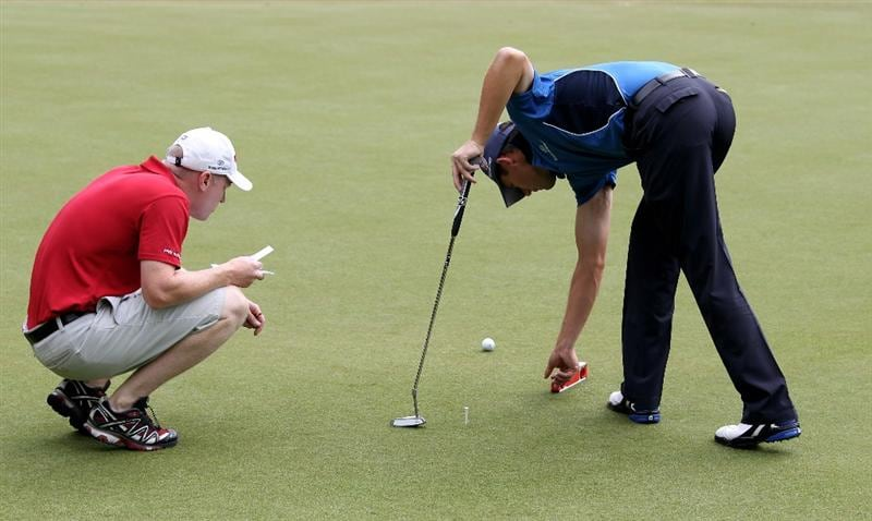 VIRGINIA WATER, ENGLAND - MAY 18:  Padraig Harrington of Ireland checks the level of a green with caddy Ronan Flood during a practice round at Wentworth prior to the BMW PGA Championship on May 18, 2010 in Virginia Water, England.  (Photo by Ross Kinnaird/Getty Images)