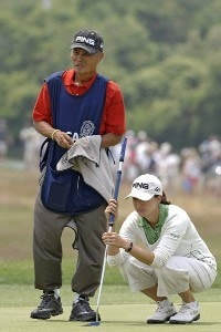 Stacy Prammanasudh lines up a putt with her caddy-father  during the third round  at Newport Country Club, site of the 2006 U. S. Women's Open in Newport, Rhode Island, July 2.Photo by Al Messerschmidt/WireImage.com