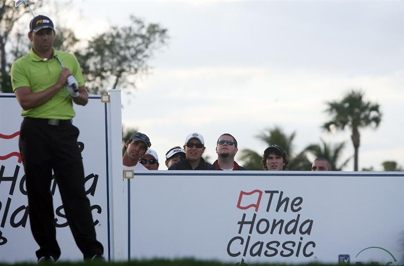 PALM BEACH GARDENS, FL - MARCH 05:  Fans peer over the logo board to watch Sergio Garcia hit his tee shot on the 17th hole during the first round of The Honda Classic at PGA National Resort and Spa on March 5, 2009 in Palm Beach Gardens, Florida.  (Photo by Doug Benc/Getty Images)