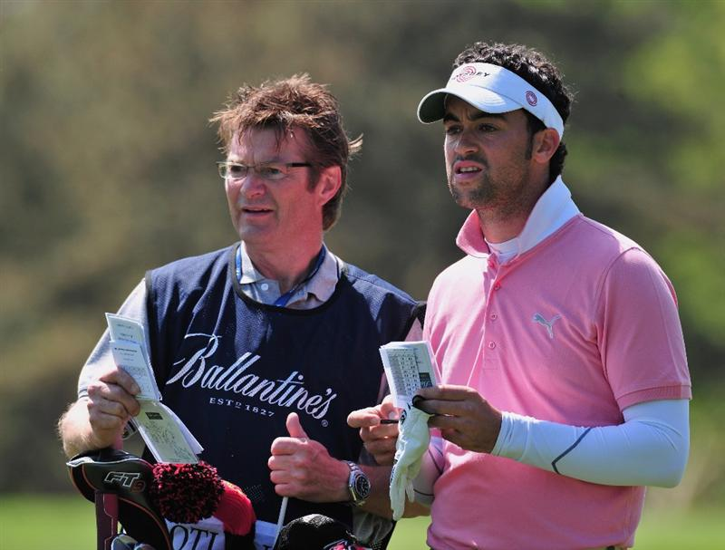 JEJU, SOUTH KOREA - APRIL 23:  Zane Scotland of England and caddie discuss his approach shot on the 15th hole during the first round of the Ballantine's Championship at Pinx Golf Club on April 23, 2009 in Jeju, South Korea.  (Photo by Stuart Franklin/Getty Images)