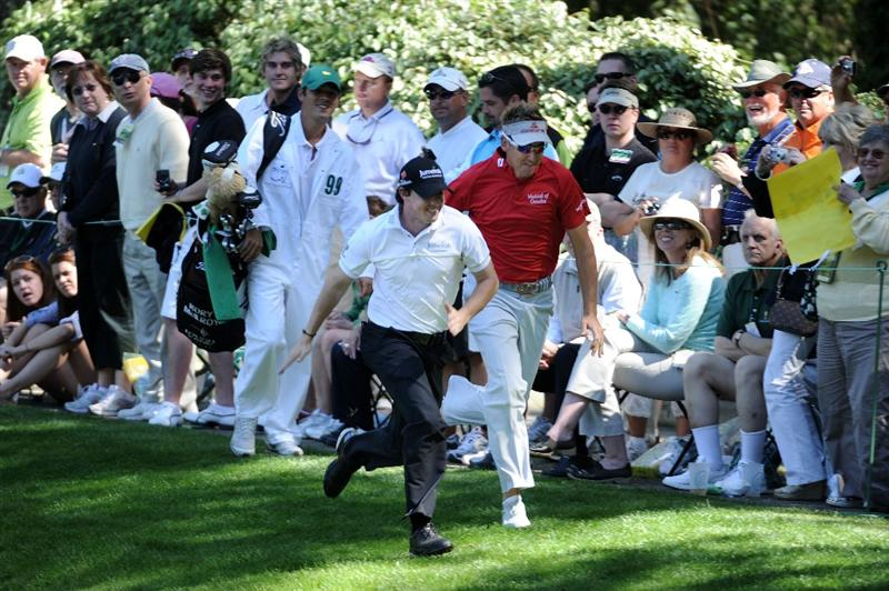 AUGUSTA, GA - APRIL 06:  Ian Poulter of England (R) and Rory McIlory of Northern Ireland (L) run as fans look on during the Par 3 Contest prior to the 2011 Masters Tournament at Augusta National Golf Club on April 6, 2011 in Augusta, Georgia.  (Photo by Harry How/Getty Images)
