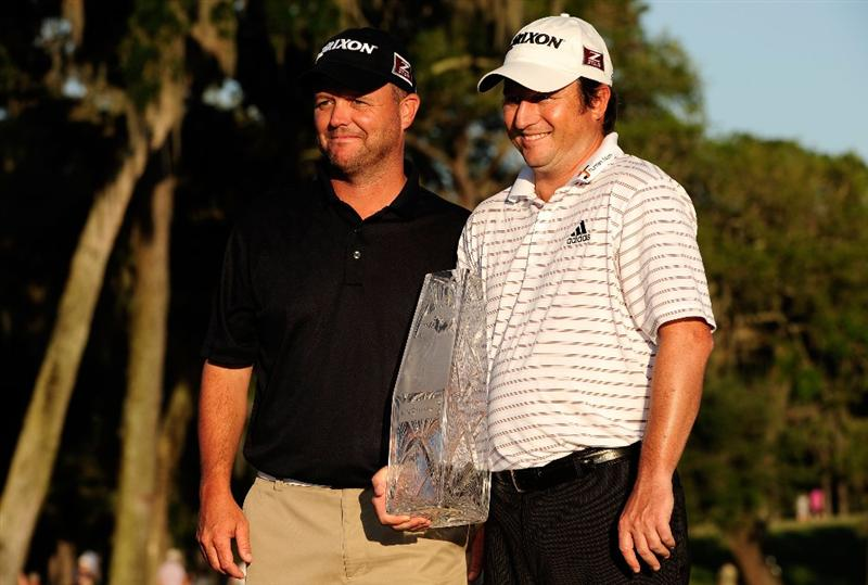 PONTE VEDRA BEACH, FL - MAY 09:  Tim Clark of South Africa smiles with his caddie Steve Burwood (R) while holding the trophy after winning THE PLAYERS Championship held at THE PLAYERS Stadium course at TPC Sawgrass on May 9, 2010 in Ponte Vedra Beach, Florida.  (Photo by Sam Greenwood/Getty Images)