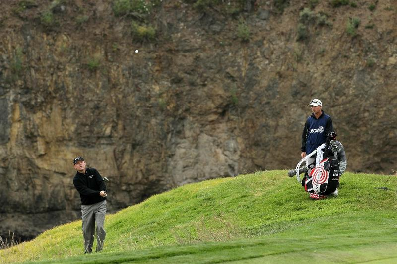 PEBBLE BEACH, CA - JUNE 18:  Shaun Micheel hits a shot on the eighth hole as his caddie Stephen Johnson looks on during the second round of the 110th U.S. Open at Pebble Beach Golf Links on June 18, 2010 in Pebble Beach, California.  (Photo by Jeff Gross/Getty Images)