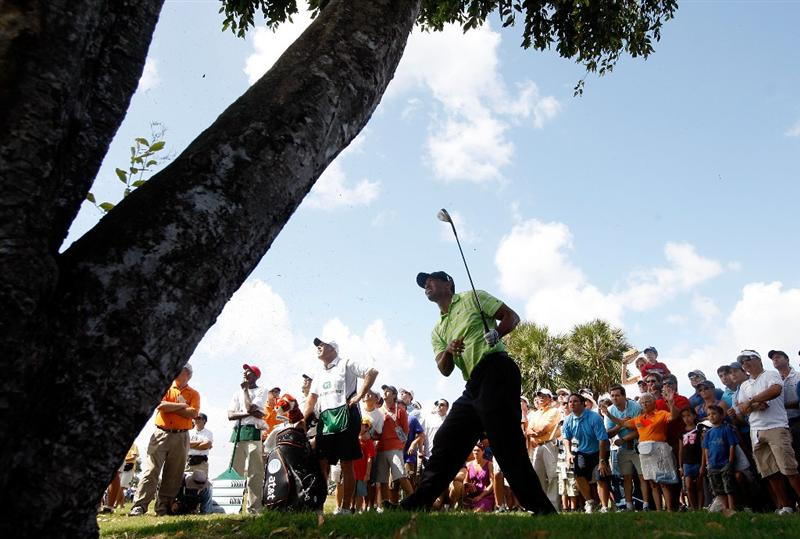 DORAL, FL - MARCH 14:  Tiger Woods hits is third shot on the 17th hole from behind a tree during the third round of the World Golf Championships-CA Championship on March 14, 2009 at the Doral Golf Resort and Spa in Doral, Florida.  (Photo by Jamie Squire/Getty Images)