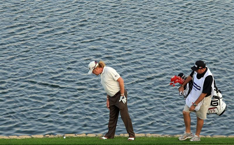 DUBAI, UNITED ARAB EMIRATES - FEBRUARY 07:  Miguel Angel Jimenez of Spain examines the lie of his ball after his third shot to the 18th green on the 1st play-off hole during the final round of the 2010 Omega Dubai Desert Classic on the Majilis Course at the Emirates Golf Club on February 7, 2010 in Dubai, United Arab Emirates.  (Photo by David Cannon/Getty Images)