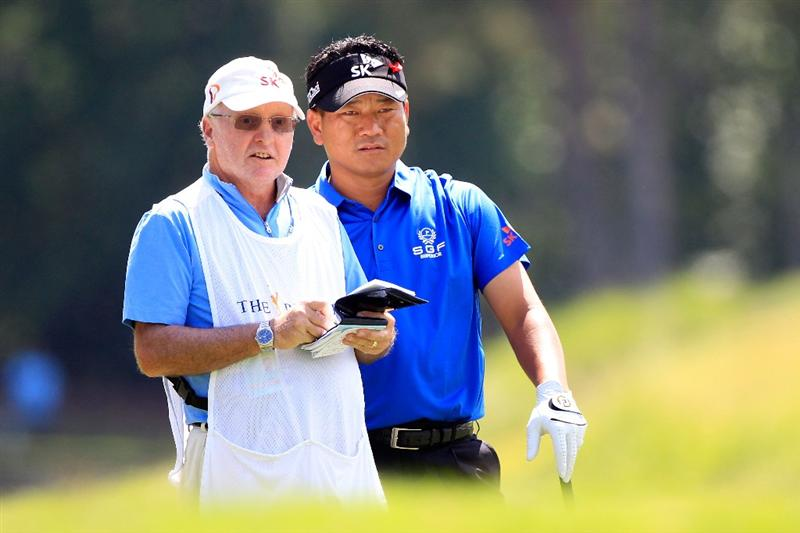PONTE VEDRA BEACH, FL - MAY 15:  K.J. Choi of South Korea (R) waits with caddies Andy Prodger (L) on the seventh hole during the final round of THE PLAYERS Championship held at THE PLAYERS Stadium course at TPC Sawgrass on May 15, 2011 in Ponte Vedra Beach, Florida.  (Photo by Sam Greenwood/Getty Images)