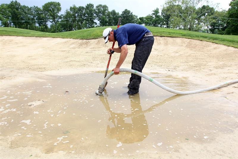 LOUISVILLE, KY - MAY 26:  A member of the grounds crew drains water from a bunker on the 10th fairway during a weather delay during the first round of the Senior PGA Championship presented by KitchenAid at Valhalla Golf Club on May 26, 2011 in Louisville, Kentucky.  (Photo by Andy Lyons/Getty Images)