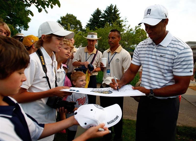 CHASKA, MN - AUGUST 10:  Tiger Woods (R) signs autographs for fans during a practice round prior to the start of the 91st PGA Championship at the Hazeltine Golf Club on August 10, 2009 in Chaska, Minnesota.  (Photo by Scott Halleran/Getty Images)
