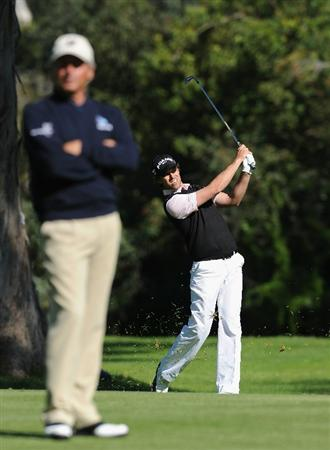 PACIFIC PALISADES, CA - FEBRUARY 20:  Aaron Baddeley of Australia plays his approach shot on the 13th hole as he is watched by playing partner Fred Couples during the final round of the Northern Trust Open at Riviera Country Club on February 20, 2011 in Pacific Palisades, California.  (Photo by Stuart Franklin/Getty Images)