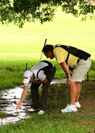 JOHANNESBURG, SOUTH AFRICA - JANUARY 09:  Danny Willett of England and his caddy Malcolm Mason look at his ball after it landed in a small stream beside the 15th green during the second round of the Joburg Open at Royal Johannesburg and Kensington Golf Club on January 9, 2009 in Johannesburg, South Africa.  (Photo by Richard Heathcote/Getty Images)