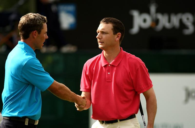 JOHANNESBURG, SOUTH AFRICA - JANUARY 11:  Charl Schwartzel and Andrew McLardy of South Africa shake hands on the 18th green after they fail to match Anders Hansen score during the final round of the Joburg Open at Royal Johannesburg and Kensington Golf Club on January 11, 2009 in Johannesburg, South Africa.  (Photo by Richard Heathcote/Getty Images)
