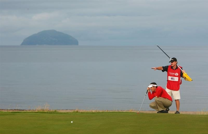 TURNBERRY, SCOTLAND - JULY 16:  Caddy John Curtis helps Anthony Wall of England with his putt on the 4th green during round one of the 138th Open Championship on the Ailsa Course, Turnberry Golf Club on July 16, 2009 in Turnberry, Scotland.  (Photo by Richard Heathcote/Getty Images)