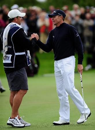 COLOGNE, GERMANY - SEPTEMBER 13:  James Kingston of South Africa is congratulated by his caddie after the winning putt on the 18th hole during the playoff against Ander Hansen of Denmark during the final round of The Mercedes-Benz Championship at The Gut Larchenhof Golf Club on September 13, 2009 in Cologne, Germany.  (Photo by Stuart Franklin/Getty Images)