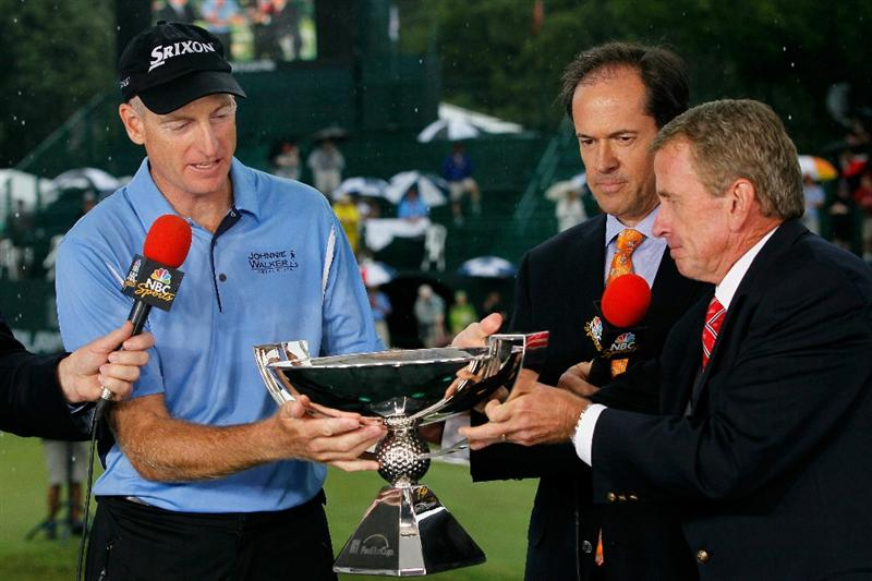 ATLANTA - SEPTEMBER 26:  PGA TOUR Commissioner Tim Finchem (R) hands the FedExCup Trophy to Jim Furyk (L) as NBC Sports Commentator Dan Hicks (C) looks on after Fuyk won THE TOUR Championship presented by Coca-Cola at East Lake Golf Club on September 26, 2010 in Atlanta, Georgia.  (Photo by Kevin C. Cox/Getty Images)