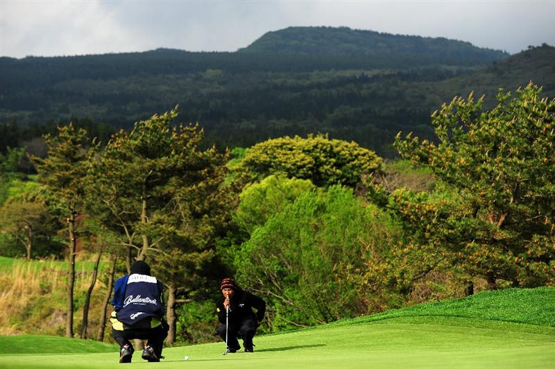 JEJU, SOUTH KOREA - APRIL 25:  Thongchai Jaidee of Thailand lines up his putt on the 14th hole during the third round of the Ballantine's Championship at Pinx Golf Club on April 25, 2009 in Jeju, South Korea.  (Photo by Stuart Franklin/Getty Images)