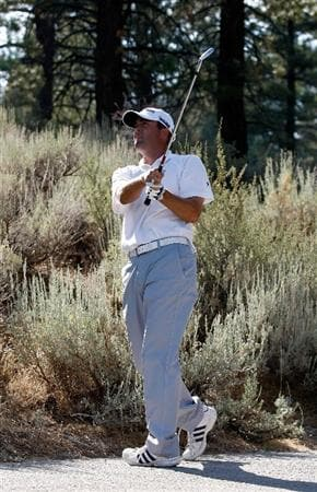 RENO, NV - AUGUST 08:  Ryan Palmer hits his second shot off the cart path on the 15th hole while wearing his caddie's tennis shoes for better grip on the concrete during the third round of the Legends Reno-Tahoe Open on August 8, 2009 at Montreux Golf and Country Club in Reno, Nevada.  (Photo by Jonathan Ferrey/Getty Images)