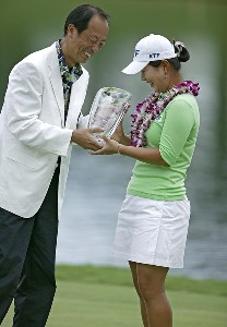 CEO Hidetoshi Yamamoto, left, of the Fields Corporation hands Meena Lee the winning trophy of the after Lee won a sudden death playoff against Seon Hwa Lee at the Fields Open in Hawaii golf tournament Feb. 25, 2006 at the Ko Olina Resort Golf Club in Kapolei, on the island of Oahu, Hawaii.Photo by Marco Garcia/WireImage.com