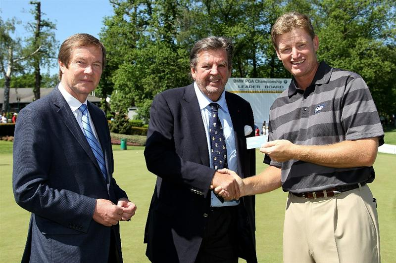 VIRGINIA WATER, ENGLAND - MAY 23:  European Tour Chief Executive George O'Grady (L) and Ernie Els (R) of South Africa (R) congratulate Johann Rupert (C) on becoming an Honorary Lifetime Vice-President of the European Tour during the final round of the BMW PGA Championship on the West Course at Wentworth on May 23, 2010 in Virginia Water, England.  (Photo by Ross Kinnaird/Getty Images)