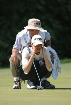 Stacy Prammanasudh lines up a putt with the help of her caddy-father, Lou, and wins  the 2005 Franklin American Mortgage Championship  May 1 in Franklin, Tn.Photo by Al Messerschmidt/WireImage.com