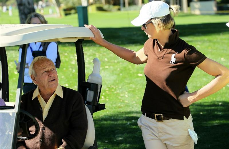 LA QUINTA, CA - JANUARY 20:  Arnold Palmer talks with Angie Watson, wife of PGA Tour golfer Bubba Watson, on the 16th hole during round two of the Bob Hope Classic at the La Quinta Country Club on January 20, 2011 in La Quinta, California. Watson was an amateur partner of Palmer's grandson, PGA Tour player Sam Saunders.  (Photo by Stephen Dunn/Getty Images)