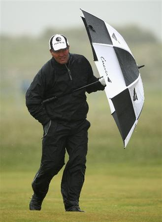BALTRAY, IRELAND - MAY 16:  Thomas Levet of France shelters from the high winds and rain on the second hole during the third round of The 3 Irish Open at County Louth Golf Club on May 16, 2009 in Baltray, Ireland.  (Photo by Andrew Redington/Getty Images)