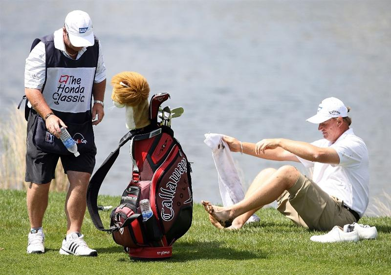PALM BEACH GARDENS, FL - MARCH 05:  With some help from his caddie, Ernie Els wipes mud off his feet after hitting out of the water hazard on the sixth fairway during the first round of The Honda Classic at PGA National Resort and Spa on March 5, 2009 in Palm Beach Gardens, Florida.  (Photo by Doug Benc/Getty Images)