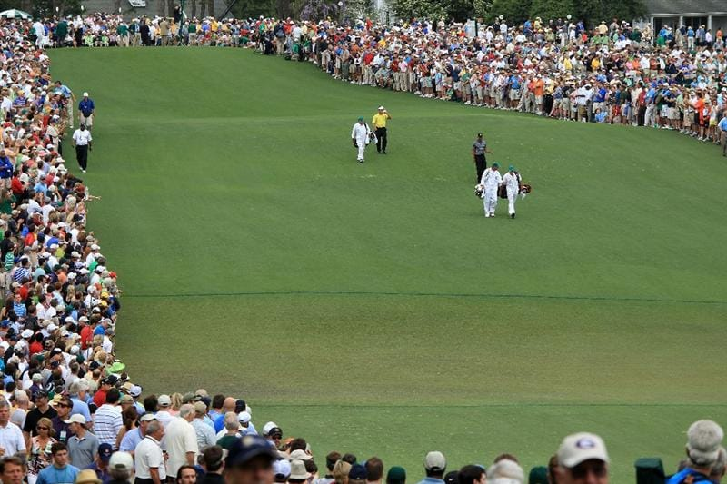 AUGUSTA, GA - APRIL 08:  Tiger Woods, Matt Kuchar and K.J. Choi of Korea walk off the first tee with their caddies during the first round of the 2010 Masters Tournament at Augusta National Golf Club on April 8, 2010 in Augusta, Georgia.  (Photo by David Cannon/Getty Images)
