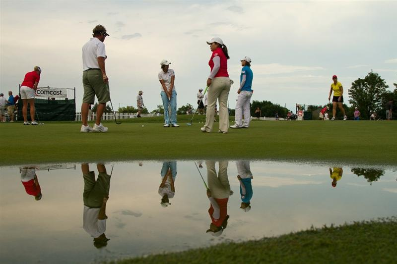 SPRINGFIELD, IL - JUNE 13: Players warming up are reflected in a puddle on the practice putting green during a weather delay in the fourth round of the LPGA State Farm Classic at Panther Creek Country Club on June 13, 2010 in Springfield, Illinois. (Photo by Darren Carroll/Getty Images)