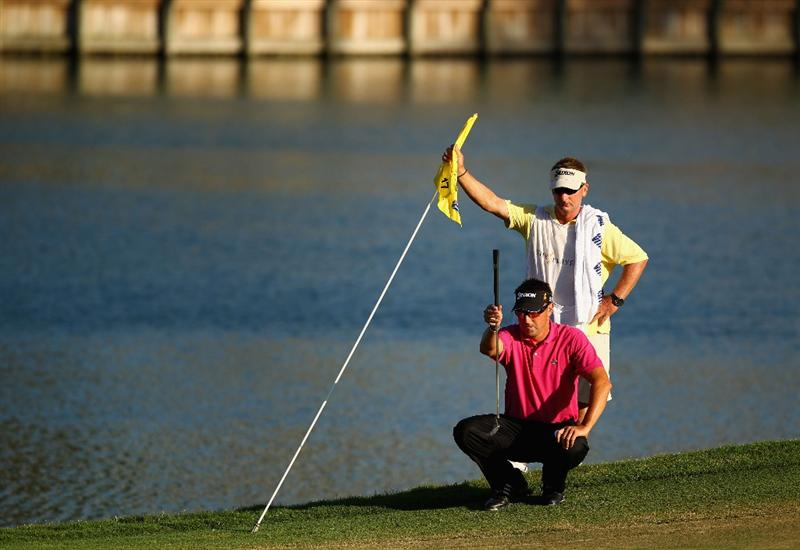 PONTE VEDRA BEACH, FL - MAY 09:  Robert Allenby of Australia lines up his putt on the 17th green with the help of his caddie Colin Burwood during the final round of THE PLAYERS Championship held at THE PLAYERS Stadium course at TPC Sawgrass on May 9, 2010 in Ponte Vedra Beach, Florida.  (Photo by Richard Heathcote/Getty Images)