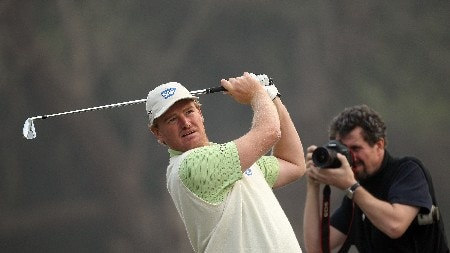 DELHI, INDIA - FEBRUARY 05:  Ernie Els of South Africa hits his tee shot to the 17th green whilst a photographer gets a close up during the Challenge Match, in the Emaar-MGF Indian Masters at the Delhi Golf Club on February 5, 2008 in Delhi, India.  (Photo by David Cannon/Getty Images)