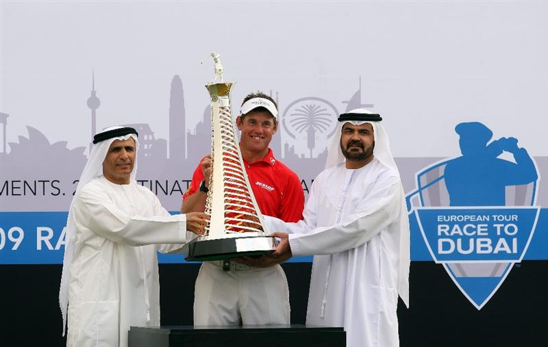 DUBAI, UNITED ARAB EMIRATES - NOVEMBER 22:  Lee Westwood of England is presented with the Race to Dubai Trophy by His Excellency Matar al Tayer Vice President of the Dubai Sports Council (left) and Muhammed Muallem Senior Vice-President and Managing Director of DP World (UAE Region) after his victory in the final round of the Dubai World Championship, on the Earth Course, Jumeirah Golf Estates on November 22, 2009 in Dubai, United Arab Emirates  (Photo by David Cannon/Getty Images)