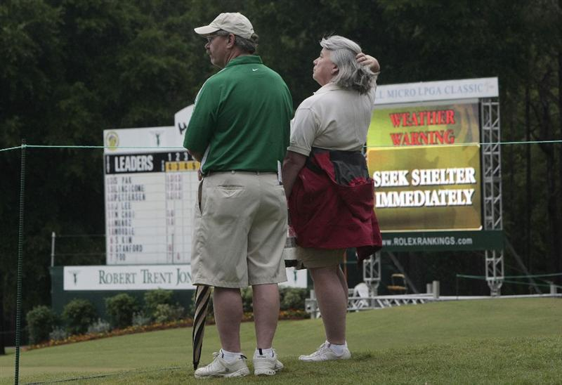 MOBILE, AL - MAY 16:  Golf fans stand near the 18th green after storms halted play during final round play in the Bell Micro LPGA Classic at the Magnolia Grove Golf Course on May 16, 2010 in Mobile, Alabama.  (Photo by Dave Martin/Getty Images)