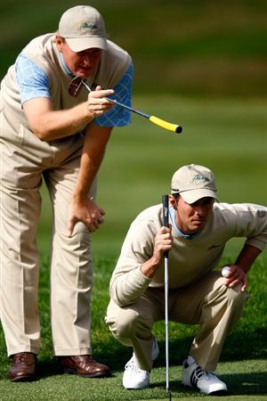 SAN FRANCISCO - OCTOBER 09:  Ernie Els (L) and Mike Weir of the International Team line up a putt on the first green during the Day Two Fourball Matches of The Presidents Cup at Harding Park Golf Course on October 9, 2009 in San Francisco, California.  (Photo by Scott Halleran/Getty Images)