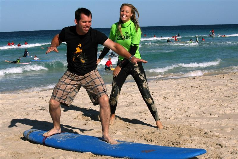 PERTH, AUSTRALIA - FEBRUARY 18:  Paul Casey of England is given a surfing lesson by Jaala Baldock a Surfing instructor for Surfing WA on Trigg Beach in Perth as a preview for the 2009 Johnnie Walker Classic tournament at the Vines Resort and Country Club, on 18 February 2009, in Perth, Australia  (Photo by David Cannon/Getty Images)