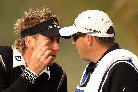 DUBAI, UNITED ARAB EMIRATES - FEBRUARY 01:  Ian Poulter of England and his caddie Terry Mundy talk during the second round of the Dubai Desert Classic on the Majlis Course held at the Emirates Golf Club on February 1, 2008 in Dubai,United Arab Emirates.  (Photo by Ross Kinnaird/Getty Images)