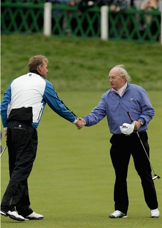 ST ANDREWS, SCOTLAND - OCTOBER 10:  Irish businessman Dermot Desmond is congratulated by his playing partner Robert Karlsson of Sweden on the 18th green during the final round of The Alfred Dunhill Links Championship at The Old Course on October 10, 2010 in St Andrews, Scotland.  (Photo by Andrew Redington/Getty Images).