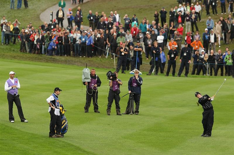 NEWPORT, WALES - OCTOBER 02:  Rory McIlroy of Europe plays an approach shot on the 18th hole as Stewart Cink of the USA looks on during the rescheduled Afternoon Foursome Matches during the 2010 Ryder Cup at the Celtic Manor Resort on October 2, 2010 in Newport, Wales.  (Photo by Ross Kinnaird/Getty Images)