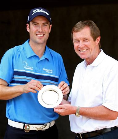 DUBAI, UNITED ARAB EMIRATES - NOVEMBER 20:  Ross Fisher of England is presented with the October Race to Dubai Golfer of the Month award by George O'Grady, Chief Executive of The European Tour during the second round of the Dubai World Championship on the Earth Course, Jumeriah Golf Estates on November 20, 2009 in Dubai, United Arab Emirates.  (Photo by Ross Kinnaird/Getty Images)