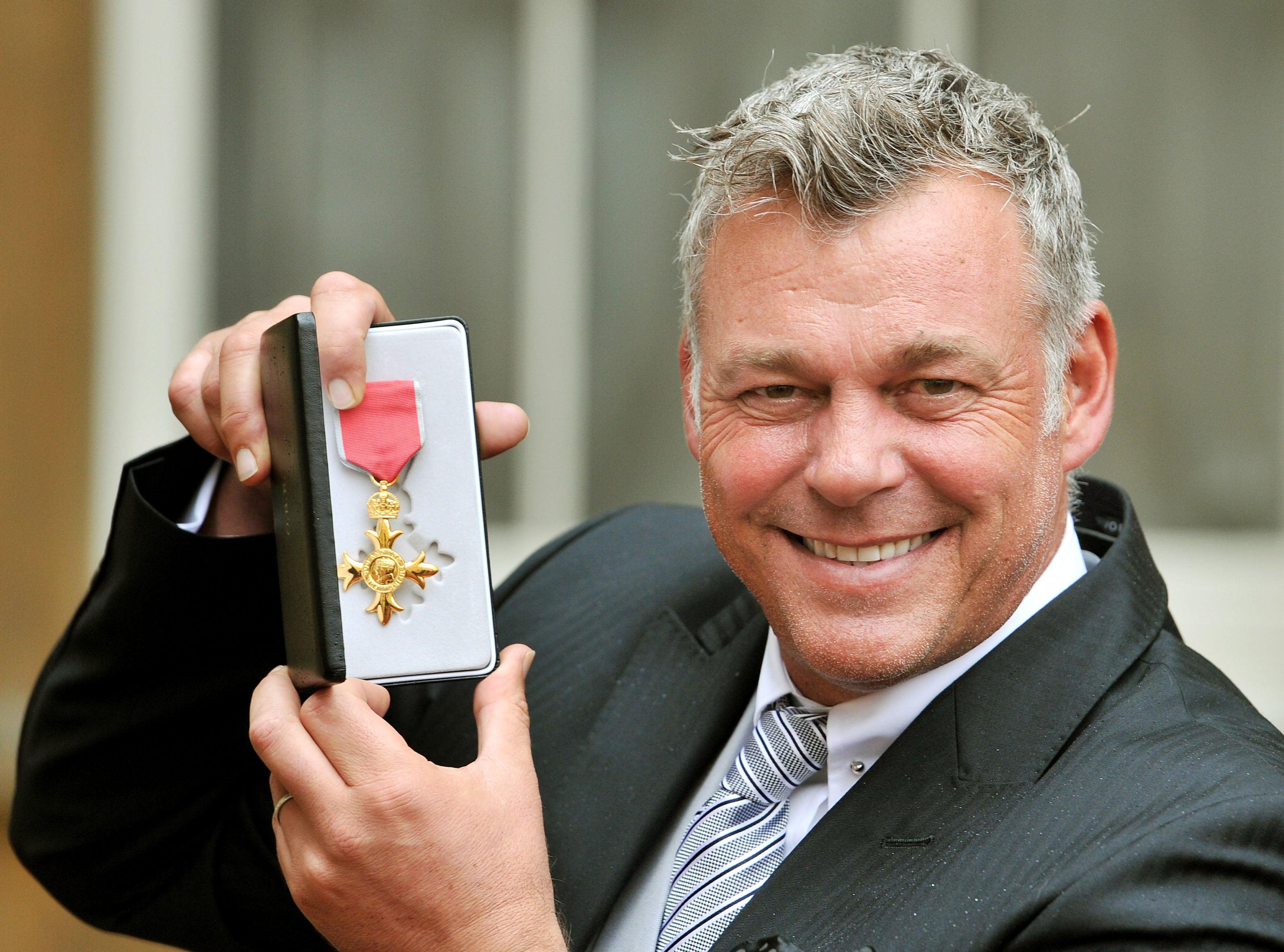 Darren Clarke with OBE medal in 2012