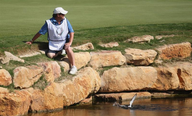 VILAMOURA, PORTUGAL - OCTOBER 16:  Caddie for Emanuele Canonica of Italy helps to rescue a pigeon from the water around the 18th green during the first round of the Portugal Masters at the Oceanico Victoria Golf Course on October 16, 2008 in Vilamoura, Portugal.  (Photo by Warren Little/Getty Images)