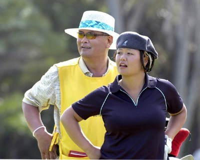 Christina Kim, and her caddy-father, Man, check the ninth green during the pro am at the 2006 SBS Open at Turtle Bay February 15 at Kahuku, Hawaii.Photo by Al Messerschmidt/WireImage.com