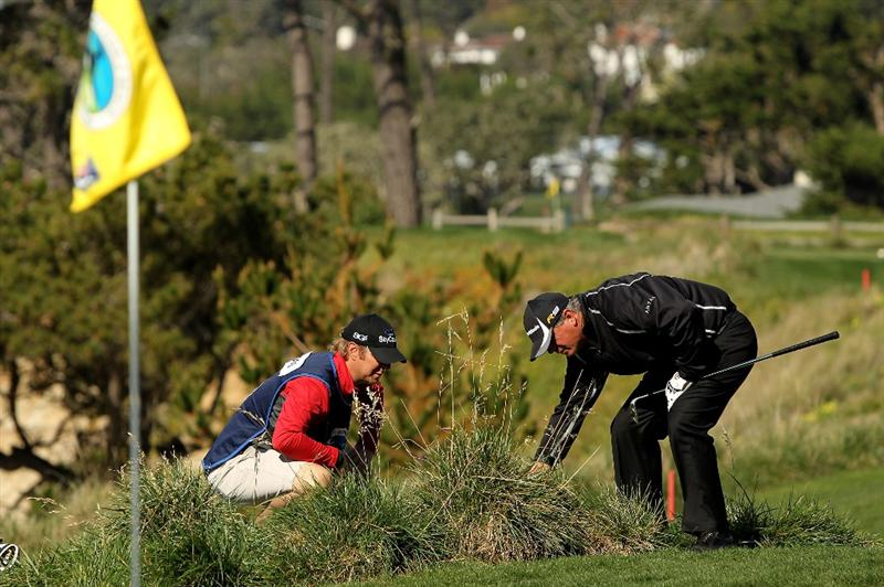 PEBBLE BEACH, CA - FEBRUARY 14:  Paul Goydos and his caddie look for his ball on the fifth hole during the final round of the AT&T Pebble Beach National Pro-Am at Pebble Beach Golf Links on February 14, 2010 in Pebble Beach, California.  (Photo by Ezra Shaw/Getty Images)